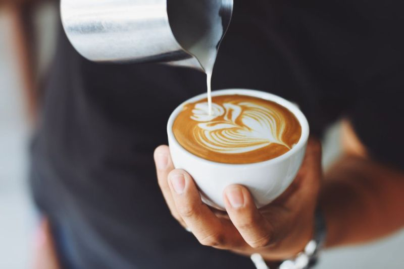 Pouring frothed milk for latte